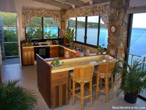 A spacious kitchen with pantry, bar and great water views - Romantic waterfront villa, private snorkeling beac