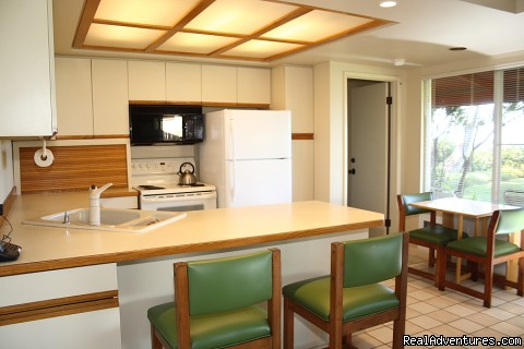 Kitchen has counter dining and a table