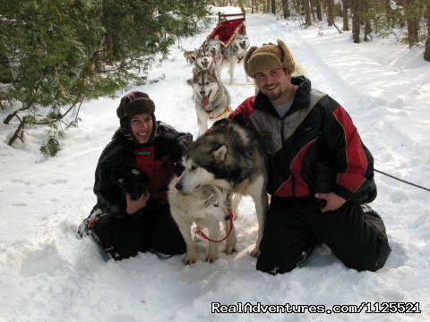 Guests having some cuddle time on the trail - Singing Dogs-Cabin Rentals