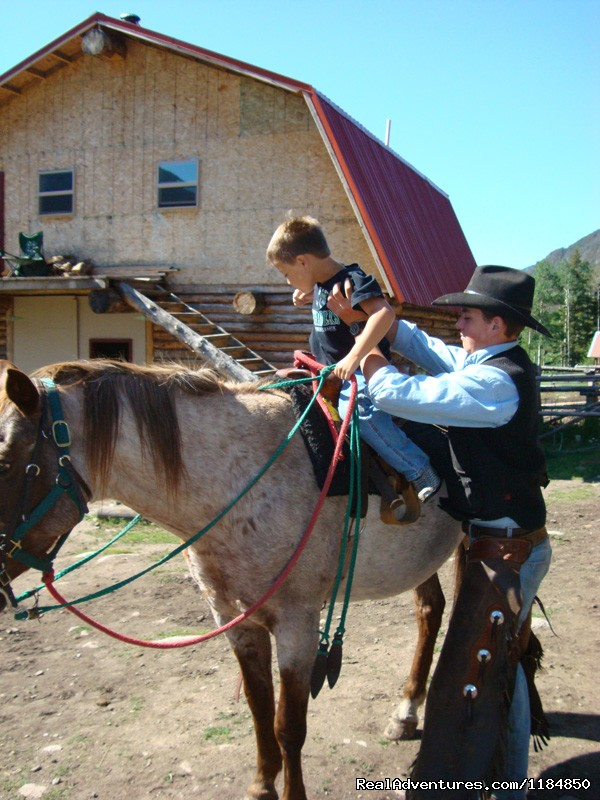 Wrangler assists a young rider | Image #8/18 | Hawley Mountain Guest Ranch Vacation