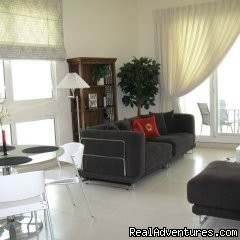 Corner 1-bed apartment sea/Marina view in Dubai: Spacious living room leading onto balcony with Marina view.