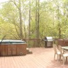 side of deck with grill, hot tub and table