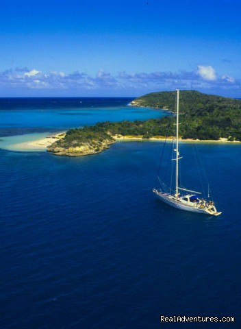 Sailing yacht anchored off white sand beach - Nicholson Yachts