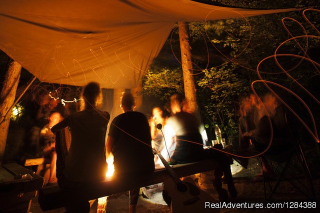 Guest evening socialising by the fireplace - Open air hostel NaturPlac